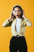 šokovala asijskou dívku naslouchající hudbě se sluchátky, izolovaná na žluté