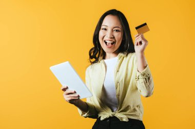 happy asian girl shopping online with digital tablet and credit card, isolated on yellow