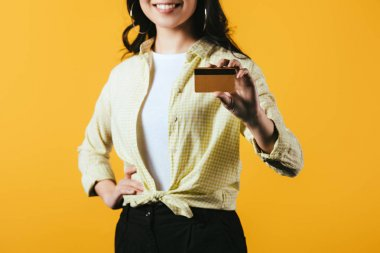 cropped view of smiling woman holding credit card, isolated on yellow