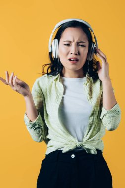confused asian girl listening music with headphones, isolated on yellow
