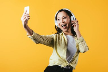 attractive asian girl taking selfie on smartphone, singing and listening music with headphones, isolated on yellow