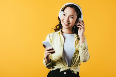 smiling asian girl listening music with headphones and smartphone, isolated on yellow