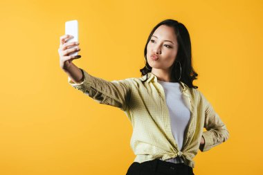 Attractive asian girl taking selfie on smartphone isolated on yellow stock vector