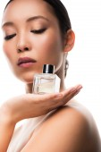 tender asian girl with closed eyes holding perfume bottle, isolated on white