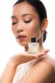 tender asian girl with closed eyes holding perfume, isolated on white