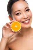 atraktivní šťastná Asijská dívka držící oranžovou, izolovanou na bílém