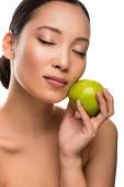 Něžná asijská žena s zavřenýma očima, která drží zelené jablko, izolovaná na bílém