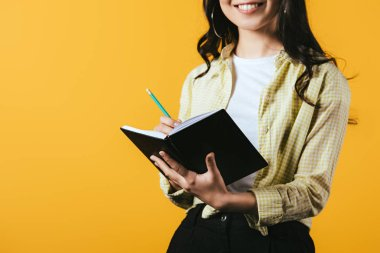 cropped view of smiling girl writing in notebook with pen, isolated on yellow