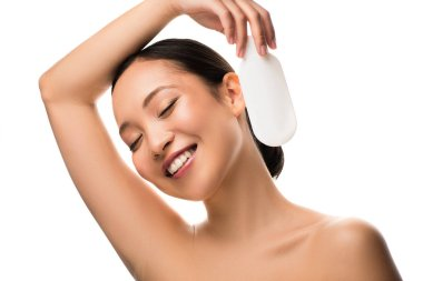 Happy asian woman with closed eyes holding bottle of lotion, isolated on white stock vector