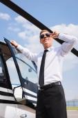 pohledný pilot při formálním nošení a slunečních brýlích s úsměvem při otvírání dveří vrtulníku