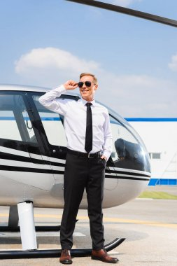 Handsome Pilot in formal wear adjusting sunglasses and smiling near helicopter stock vector