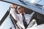 Fotografie handsome Pilot in sunglasses and formal wear opening door while sitting in helicopter cabin