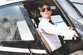sebevědomý pilot s brýlemi a formálním oblečením sedícího v kabině vrtulníků