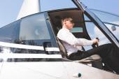 Fotografie dobře vypadající pilot s brýlemi a formálním oblečením sedícího v kabině vrtulníků