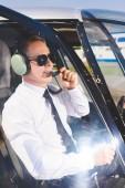 Fotografie zralý pilot z brýlí, formální opotřebení a headset sedící v kabině vrtulníků