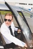 Fotografie handsome Pilot in sunglasses and formal wear sitting in helicopter cabin and opening door