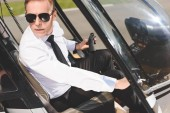 handsome Pilot in sunglasses and formal wear sitting in helicopter cabin and holding wheel