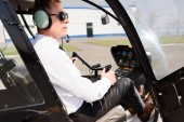 Pilot v paprskových brýlích a náhlavní soupravě, sedící v kabině helikoptéry