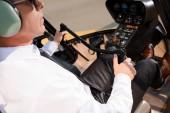 zralý pilot ve formálním opotřebení sedící v kabině vrtulníků a v hodící kolo