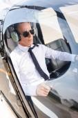 zralý pilot ve formálním oblečení a náhlavní soupravě sedící v kabině vrtulníků