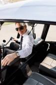 usměvavý pilot ve formálním opotřebení a slunečních brýlích sedícího v kabině vrtulníků