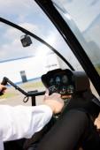 oříznutý pohled pilota na formální opotřebení sedící v kabině vrtulníků a přidržování kola