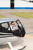 zralý pilot ve formálním opotřebení a slunečních brýlích sedícího v kabině helikoptéry s otevřenými dveřmi