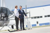 Fotografie Pilot in formal wear and businessman with suitcase near helicopter