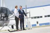 Fotografie Pilot ve formálním oblečení a obchodník s kufříkem v blízkosti helikoptéry