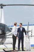 Pilot ve formálním oblečení a obchodník s kufříkem v blízkosti helikoptéry