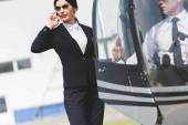 Žena ve formálním nošení hovořit na smartphone poblíž vrtulníku s pilotem