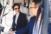 Photo businesswoman and businessman in formal wear sitting in helicopter cabin