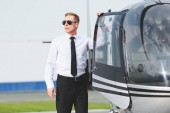 Photo Pilot in formal wear and sunglasses looking away near helicopter