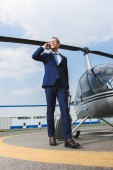 Fotografie businessman in formal wear with suitcase talking on smartphone near helicopter