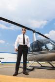 Fotografie pohled nízkého úhlu pilota ve formálním opotřebení a slunečních brýlích poblíž vrtulníku