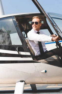 Smiling Pilot in sunglasses and formal wear sitting in helicopter cabin and holding wheel stock vector
