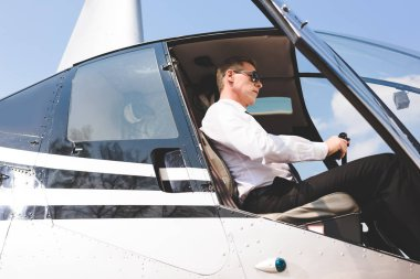 good-looking Pilot in sunglasses and formal wear sitting in helicopter cabin