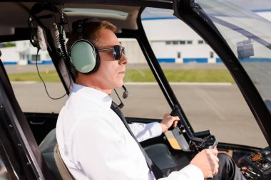 Mature Pilot in sunglasses and headset sitting in helicopter cabin and holding wheel stock vector