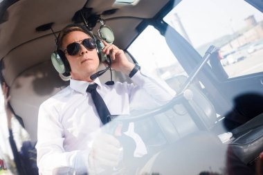 mature Pilot in sunglasses and headset with microphone sitting in helicopter cabin