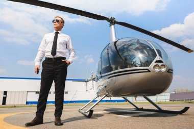 Pilot in formal wear and sunglasses posing with Hand In Pocket near helicopter stock vector