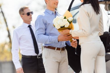 cropped view of husband giving flowers to wife on romantic date near helicopter and pilot