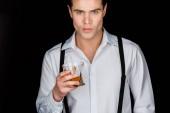jóképű férfi fehér inget és harisnyatartó gazdaság pohár whiskyt izolált fekete