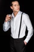 jóképű férfi fehér inget és harisnyatartó gazdaság pohár whisky állva kézzel a zsebében izolált fekete