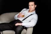 confident man holding glass of whiskey and sitting in armchair isolated on black