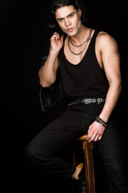 handsome man holding leather jacket and looking at camera while sitting on chair isolated on black