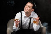 happy man sitting in armchair and holding glass of whiskey and cigar on black with smoke