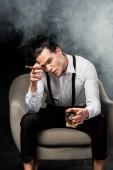 csinos ember nézi a kamerát és a gazdaság pohár whisky és a szivar fekete, füst