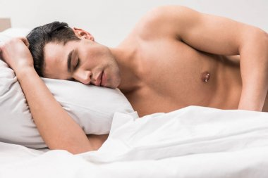 handsome and muscular man lying on bed with closed eyes