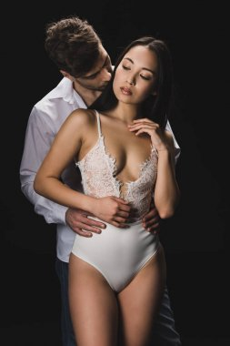handsome young man embracing and kissing attractive asian girlfriend in white lingerie isolated on black