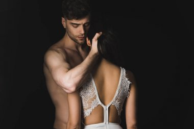 handsome shirtless man hugging sexy girlfriend in white lingerie isolated on black